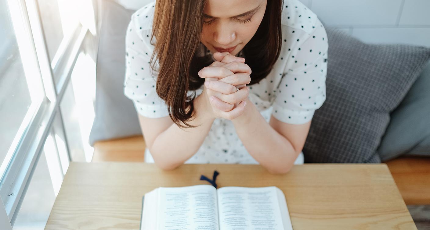 Asian woman praying with bible