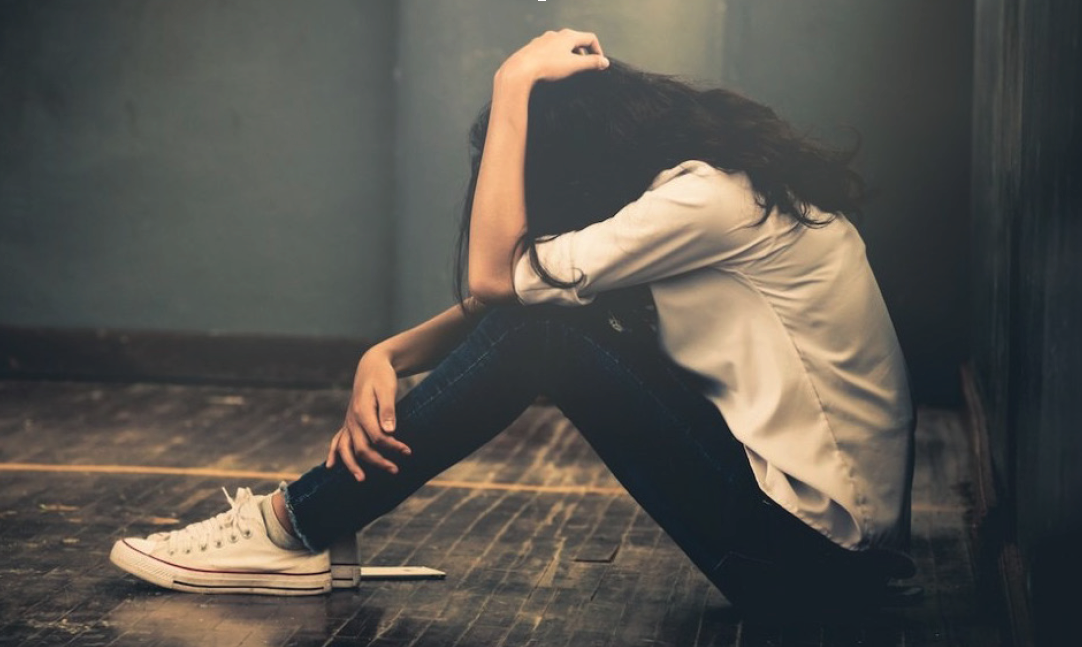 depressed young lady sitiing on the floor wiht her head down embracing her legs with one arm and her head wiht the other arm