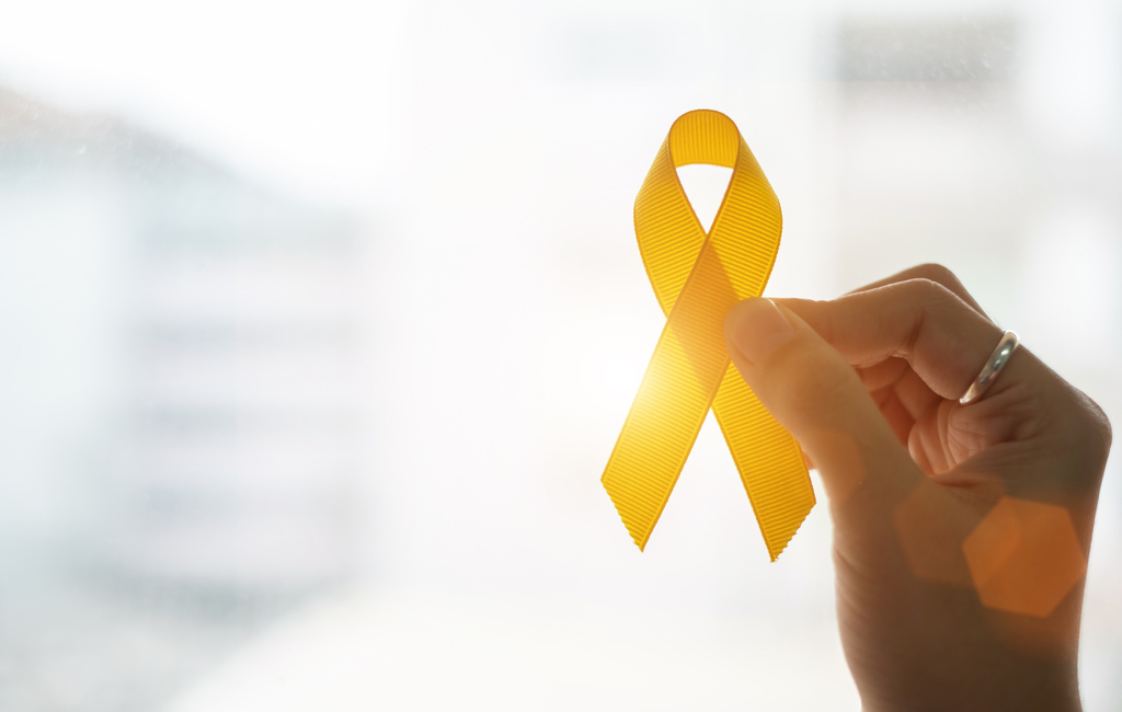 a hand holding a yellow ribbon in front of the sunlight