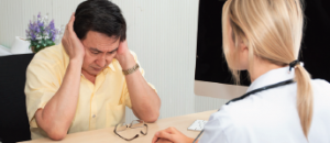 A man sitting before a doctor he takes off his glasses and places his hands on his head he is very afraid and concerned