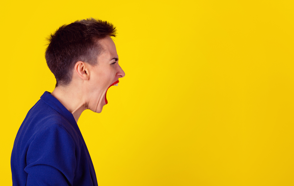 a side picture of a woman screaming to the top of her lungs in front of a yellow background