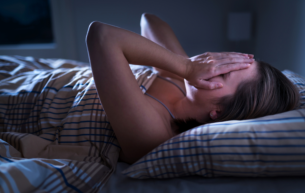 A woman laying in bed frustrated with her hands covering her face because she is unable to sleep