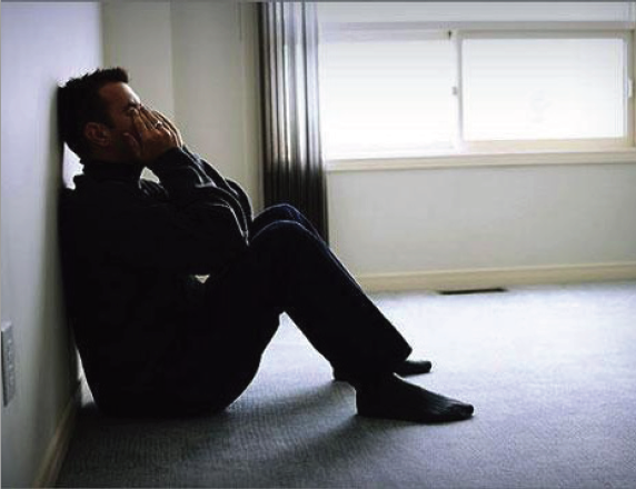Man sitting on floor with his back leaning on the wall, his head down and his hands covering his face