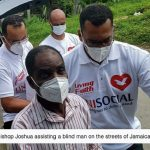 Bishop Joshua assists a blind man on the streets of Jamaica