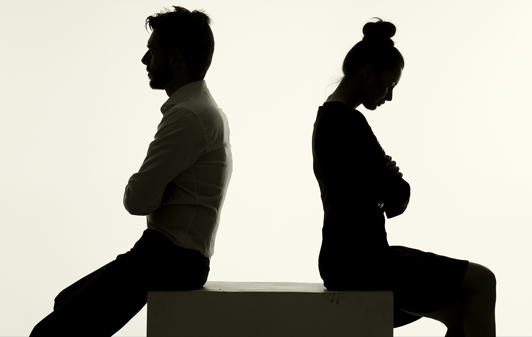 silhouette of a couple sitting with their backs to each other and arms crossed looking downcast